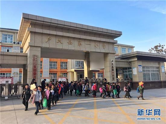 卢氏县第一小学学生放学后走出校门(2018年12月18日摄)