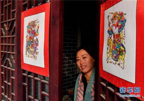 1月8日,在开封市朱仙镇,一位游客打开贴有木版年画的门。