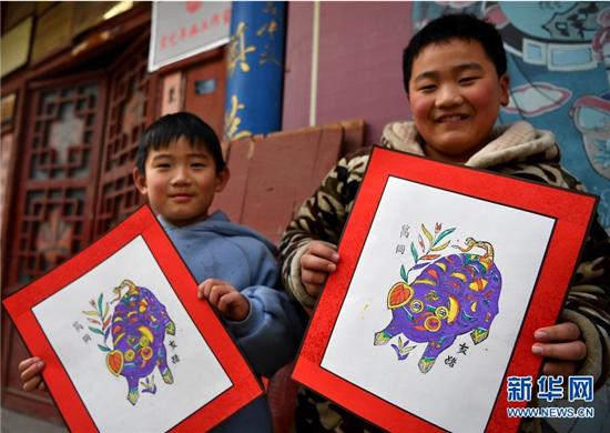 1月8日,在开封市朱仙镇,两名小朋友在展示装裱好的木版年画成品。