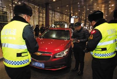 昨日,首都机场三号航站楼四层12号门前,市交通执法总队首都机场执法小年夜队队员对非法营运车辆举办检查。新京报记者 王贵彬 摄