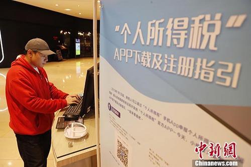 资料图:1月3日,市民在位于上海市静安嘉里中心内的个人所得税基础信息采集点进行相关信息登记。 中新社记者 殷立勤 摄