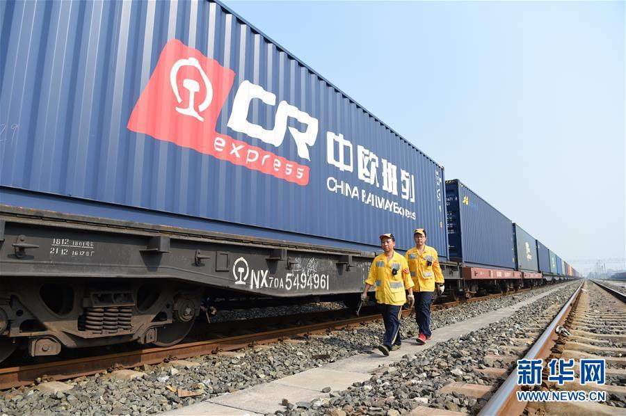 在位于重庆沙坪坝区的兴隆场上行出发作业场,进行列检作业的两名货车检车员从中欧班列旁走过(2018年8月29日摄)。新华社记者 唐奕
