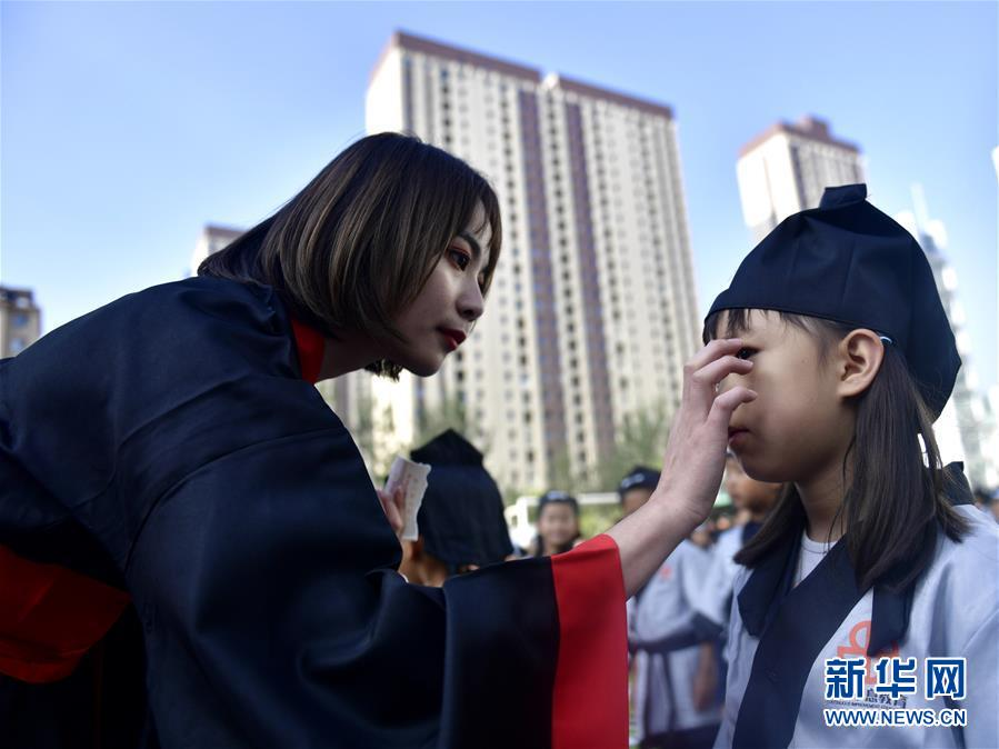 """9月1日,青海省西宁市文汇小学的老师在给一年级的学生""""朱砂启智""""。新华社记者 张龙"""