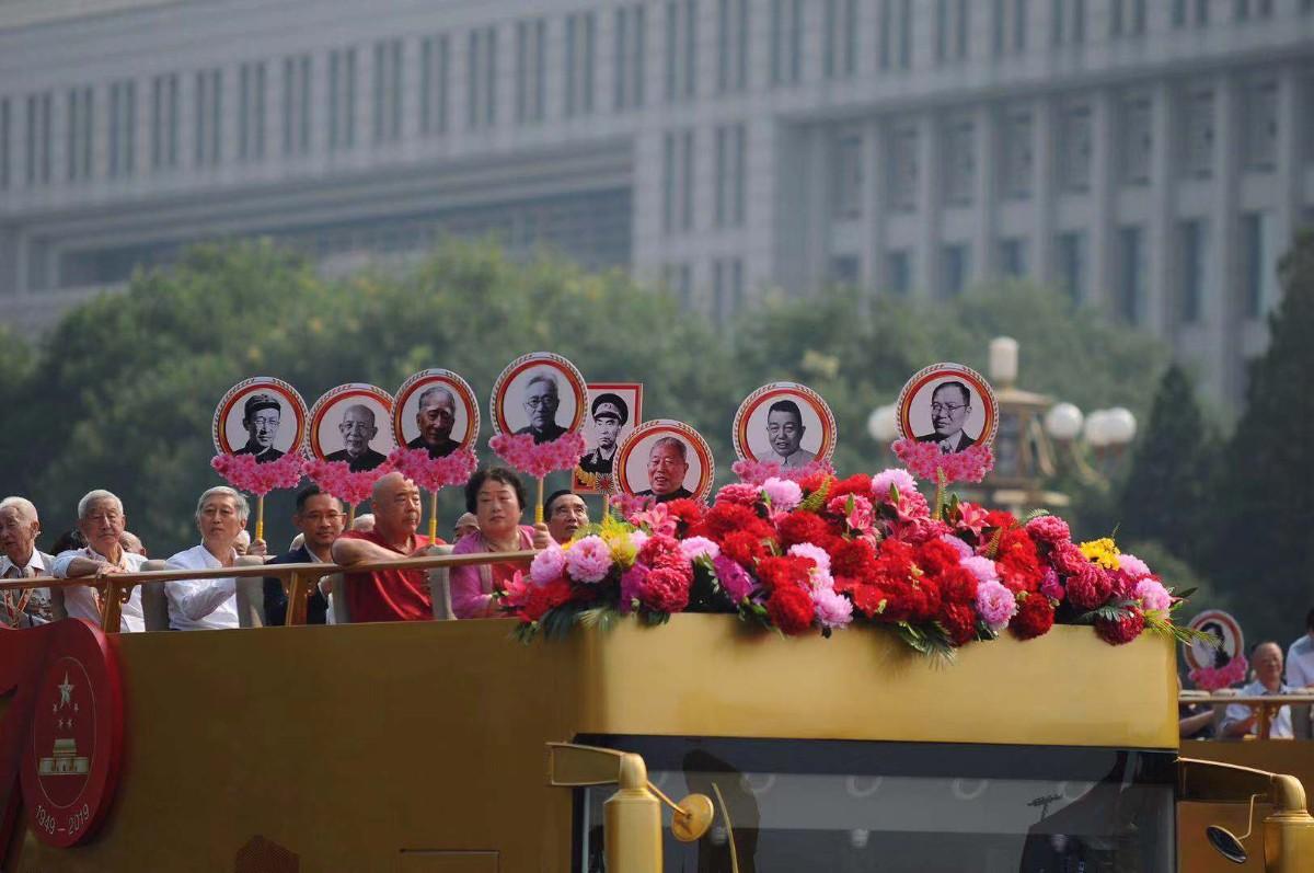 """当""""致敬""""方阵走过时,一个场景突然让人泪崩!程开甲、于敏……一张张照片上,是那些为伟大祖国献身、为人民幸福生活奋斗终生的已故建设者。他们的家人高举照片荣誉牌,在礼宾车上驶过天安门广场。"""