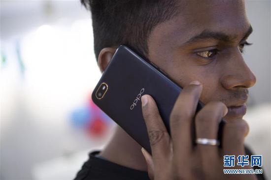 这是在印度金奈的一家商场,一名男子使用中国品牌OPPO的手机(2019年10月8日摄)。 新华社记者 吕小炜 摄