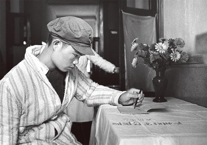 """麦贤得在""""八六""""海战中头部负重伤,他以超人的毅力和坚强的意志,坚持战斗,直到取得胜利。通过医务人员的精心治疗和护理,他的身体逐渐恢复。图为1966年麦贤得伤愈后,右手运动还不方便,他以视物化如归的精神,演习用左手写字。 新华社 邹健东/摄"""
